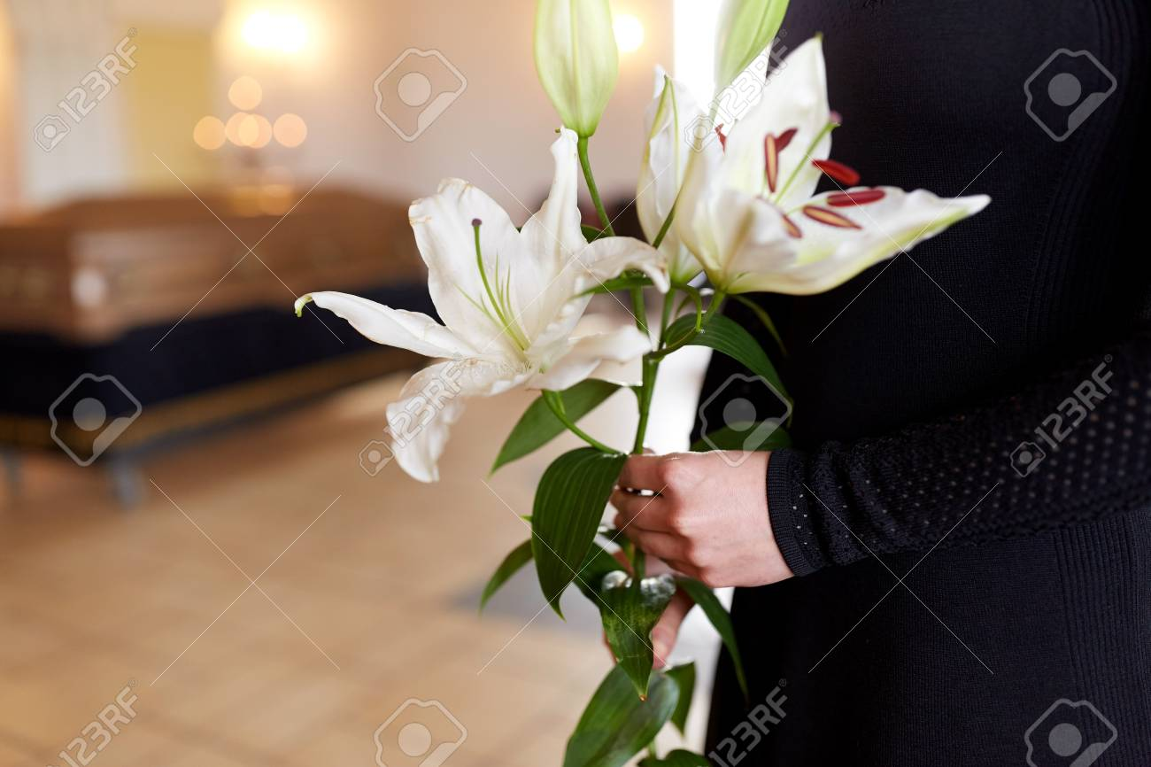 Close Up Of Woman With Lily Flowers At Funeral Stock Photo Picture