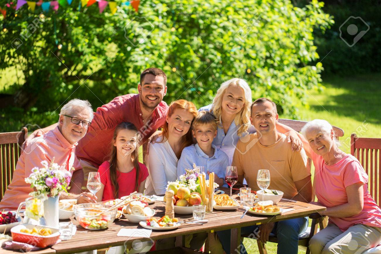 leisure, holidays and people concept - happy family having festive dinner or summer garden party - 83500327