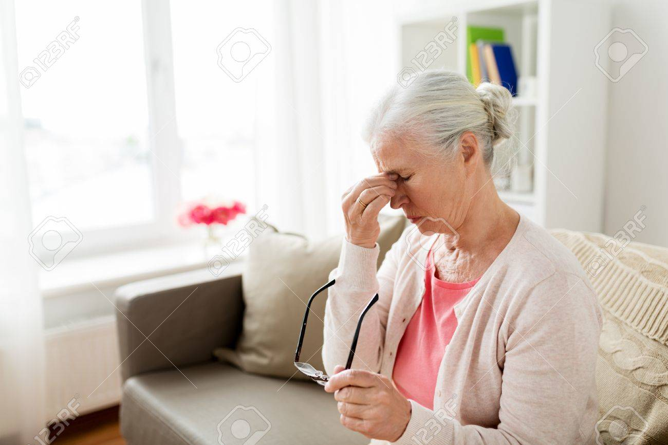 senior woman with glasses having headache at home - 83742000