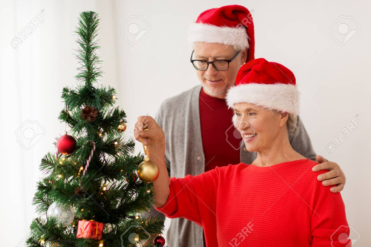 Gente Feliz En Navidad.Vacaciones Y Concepto De La Gente Feliz Pareja Sonriente Sonriendo En Sombreros De Navidad Que Conducen El Juguete De Los Ninos En Casa