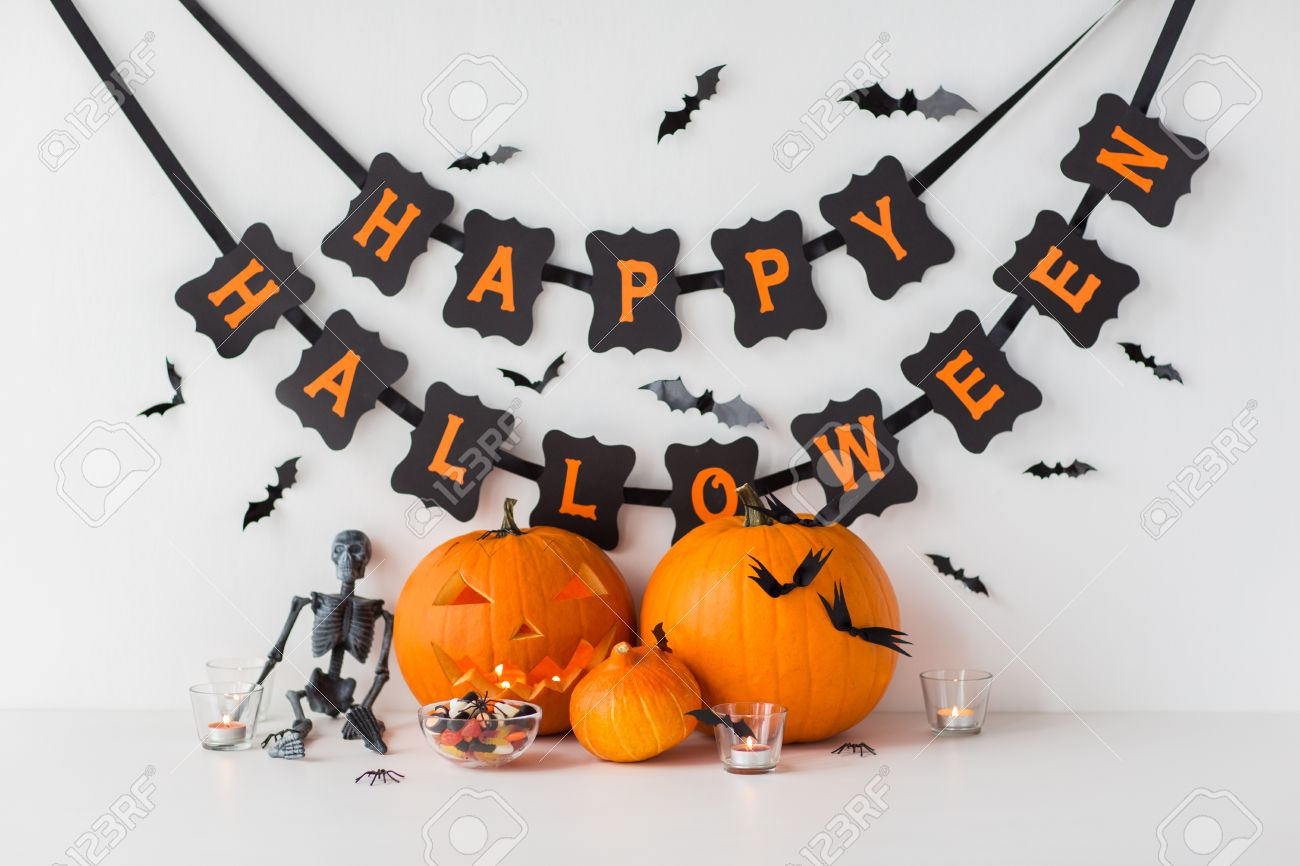 carved pumpkins with candies and halloween garland - 87040156