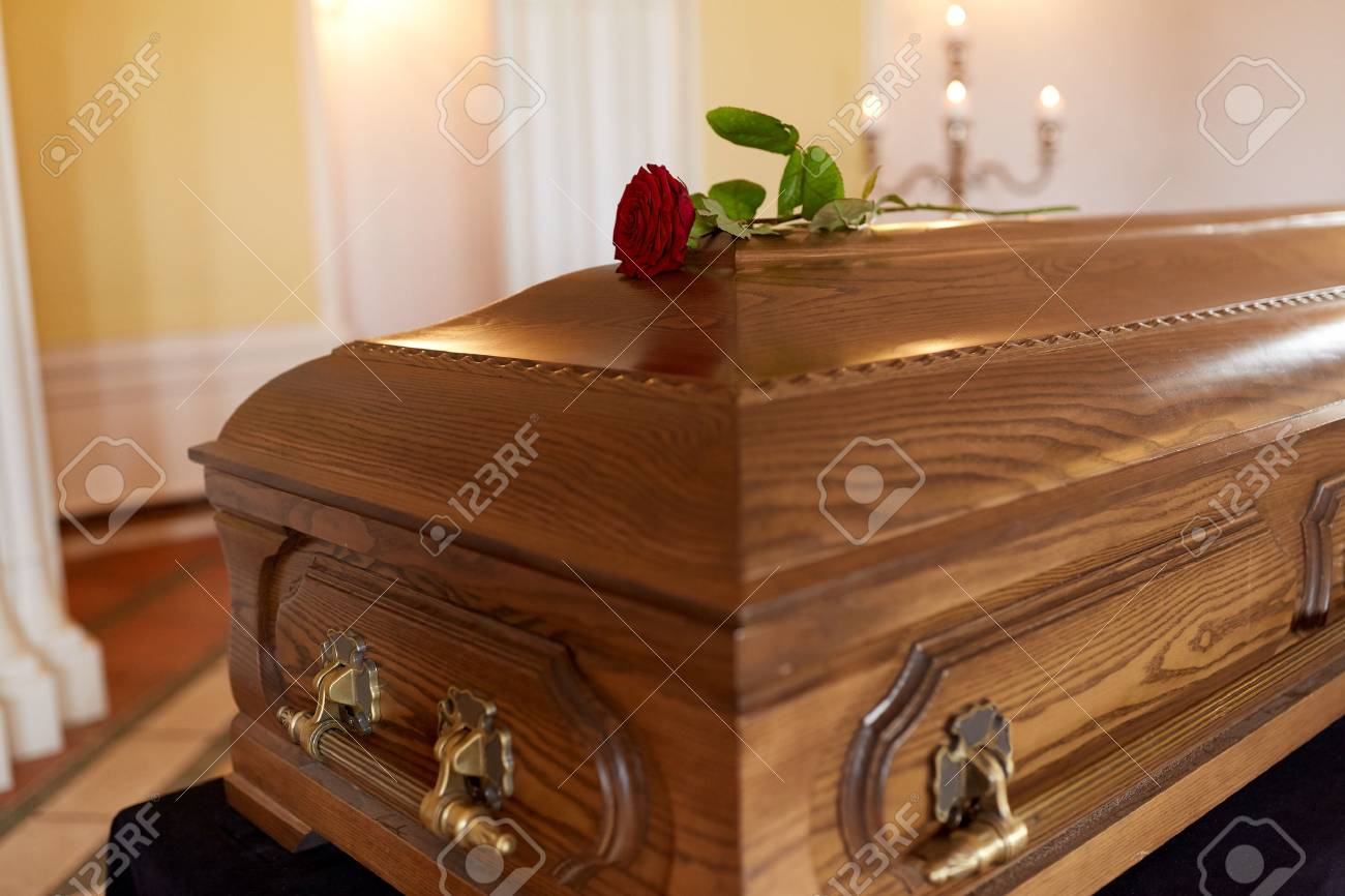 funeral and mourning concept - red rose flower on wooden coffin in church - 88451169