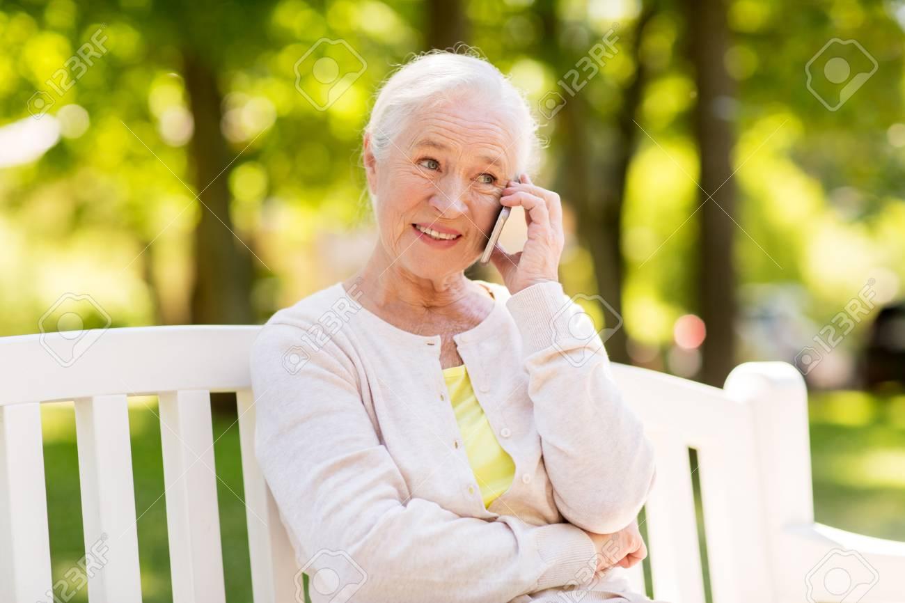 happy senior woman calling on smartphone in summer - 89431016