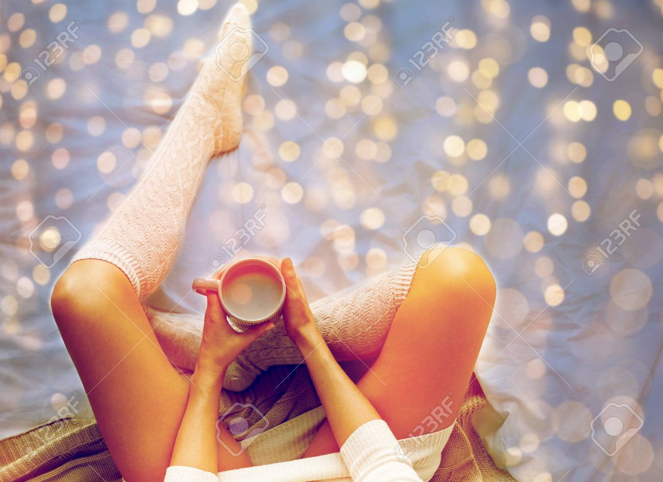 close up of woman with cocoa cup in bed at home - 89831487