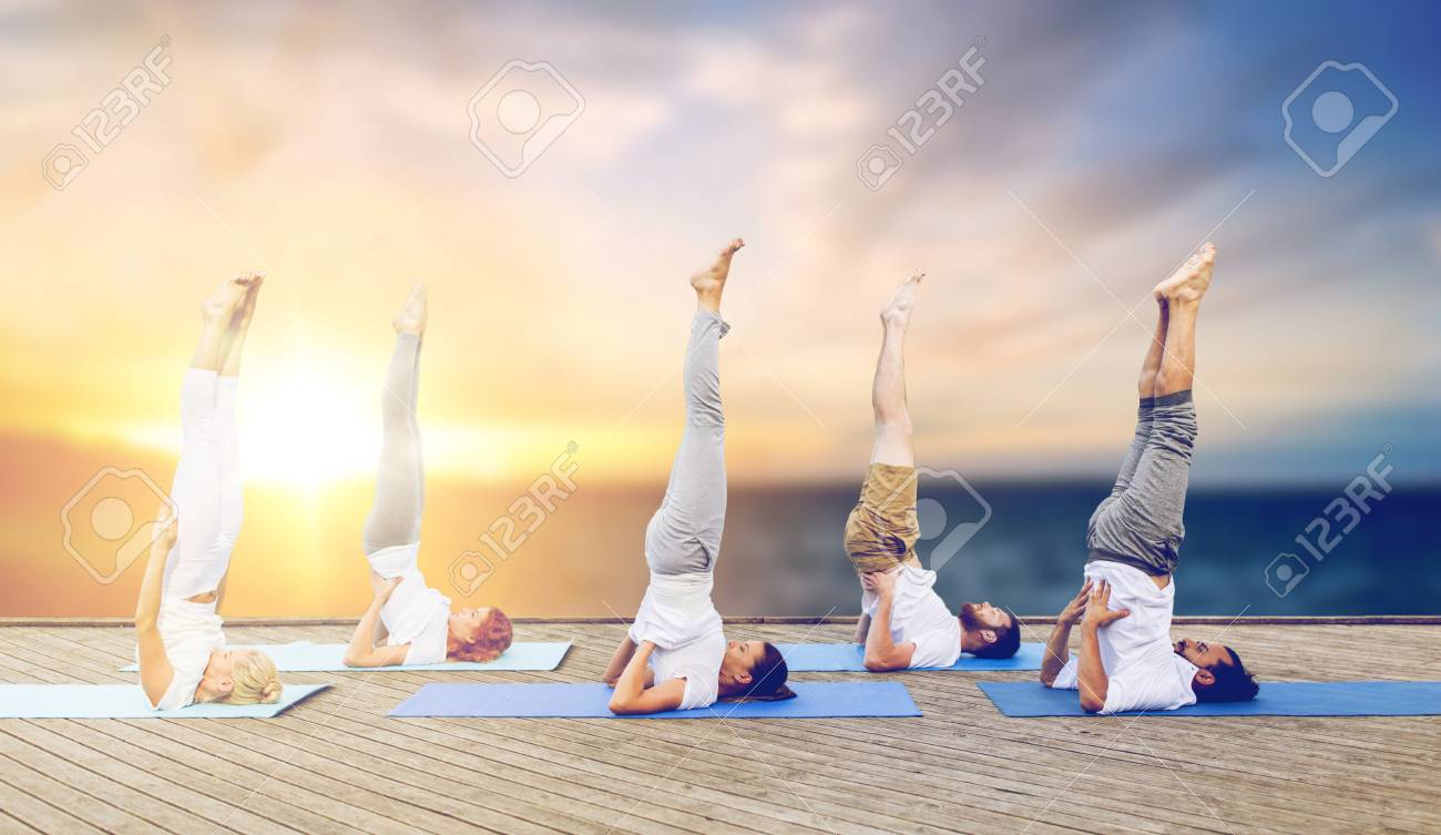 People Doing Yoga Shoulderstand On Mat Outdoors Stock Photo