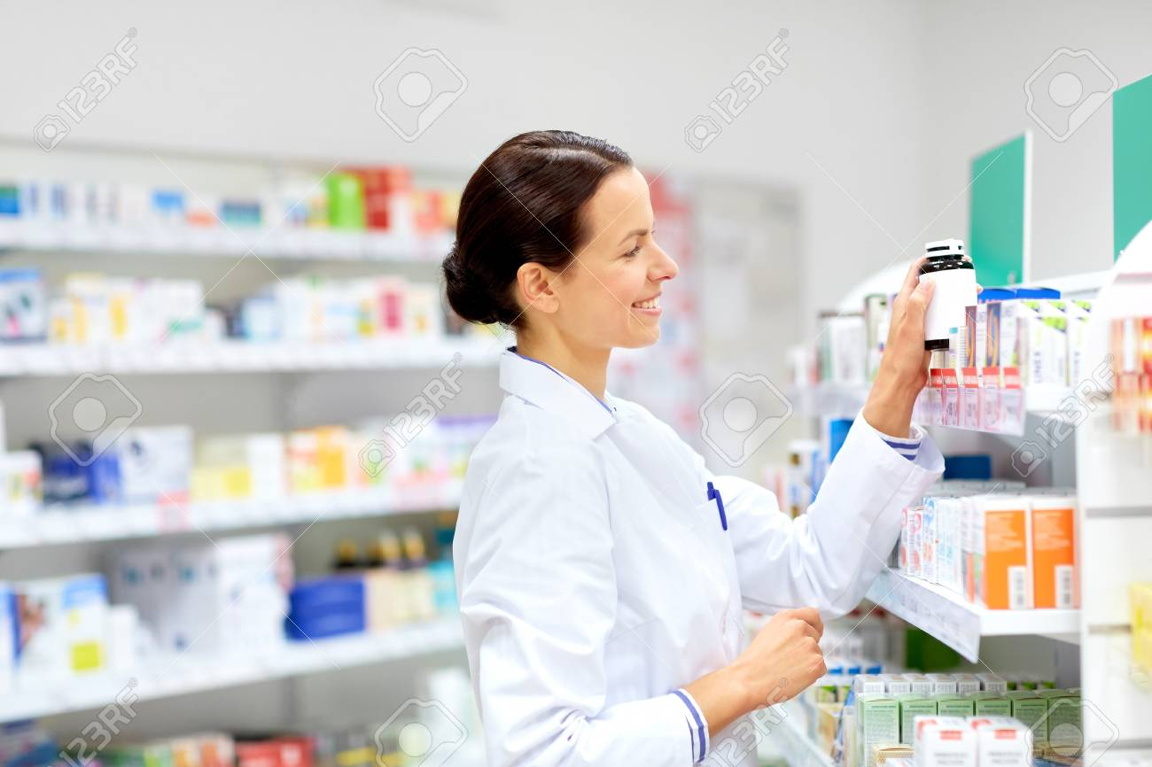 happy female apothecary with drug at pharmacy - 98073280