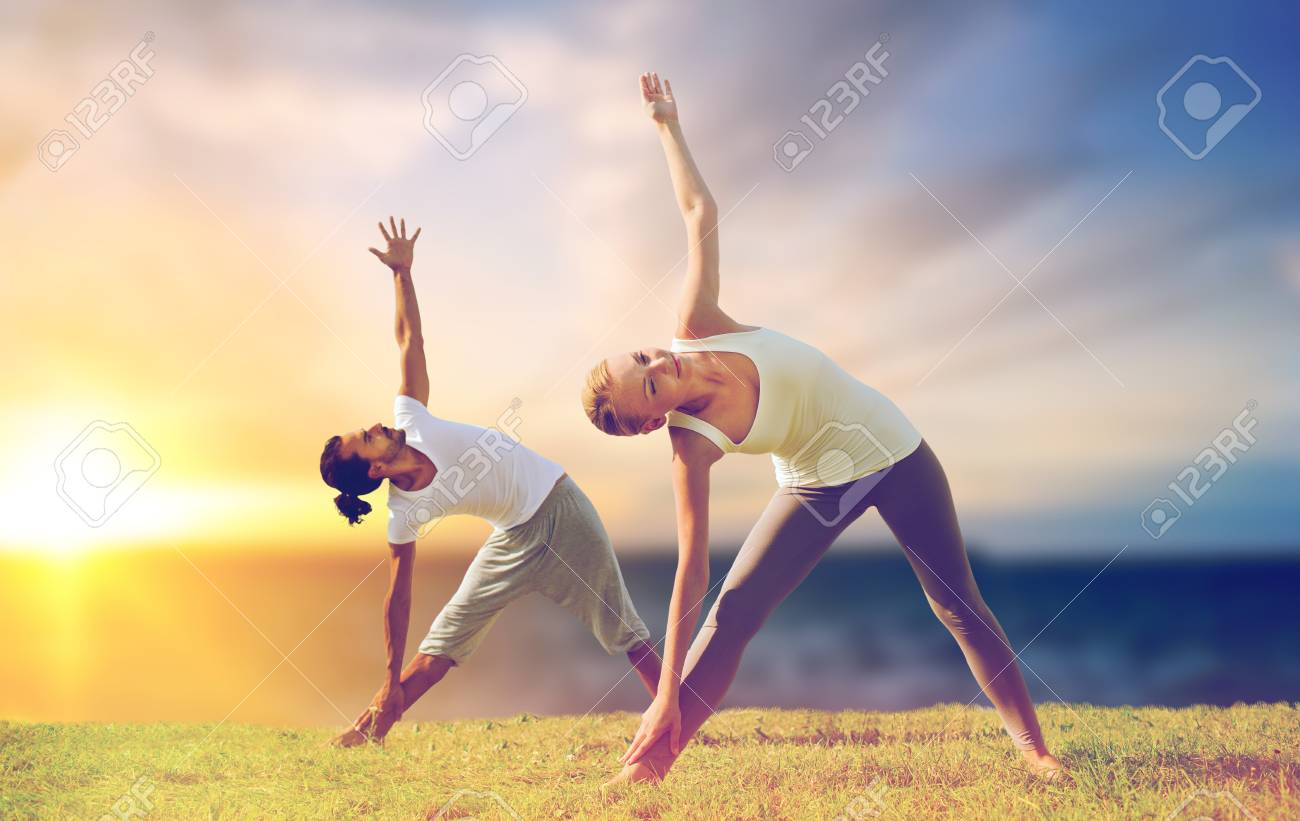 Couple Making Yoga Triangle Pose Outdoors Stock Photo