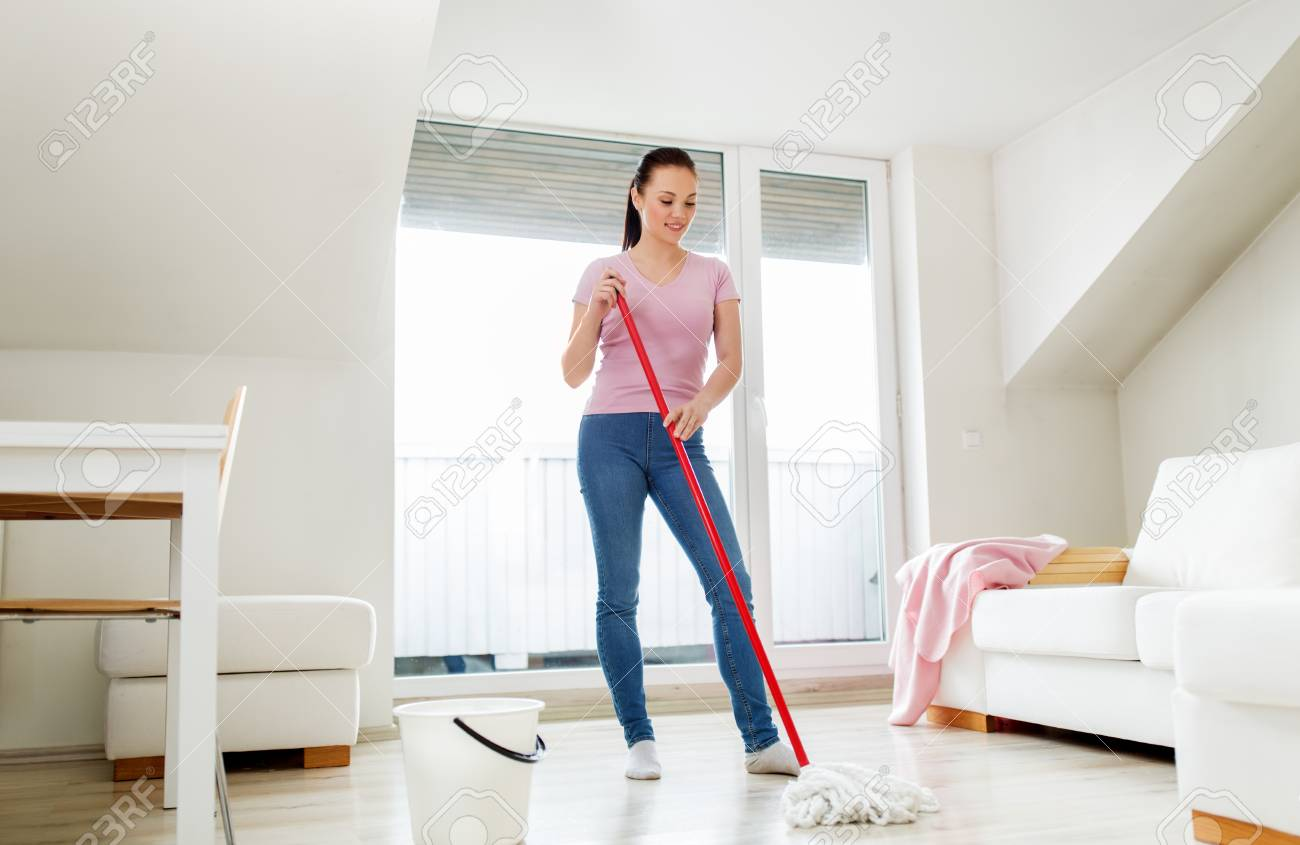 woman or housewife with mop cleaning floor at home