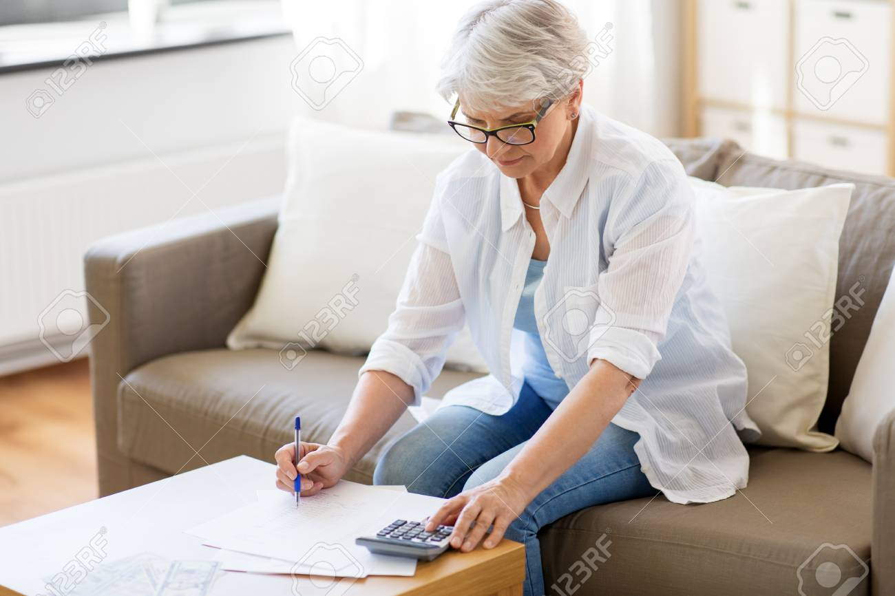 senior woman with papers and calculator at home - 104173759