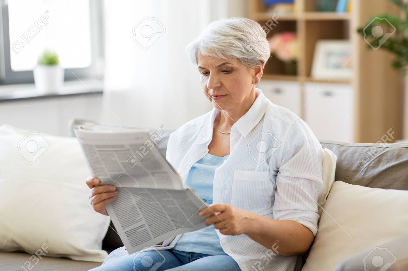 age and people concept - senior woman reading newspaper at home