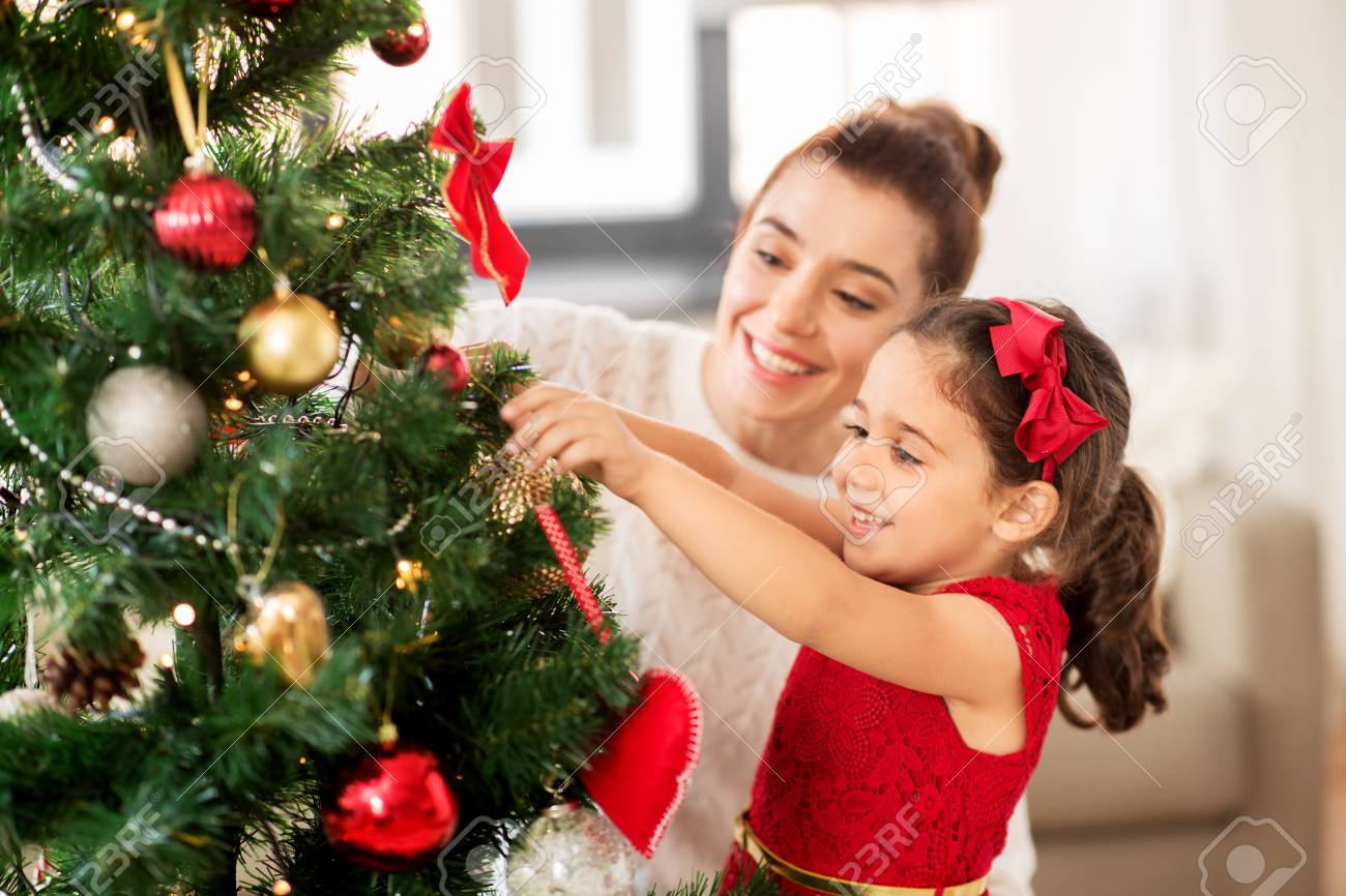 happy family decorating christmas tree at home - 107861655