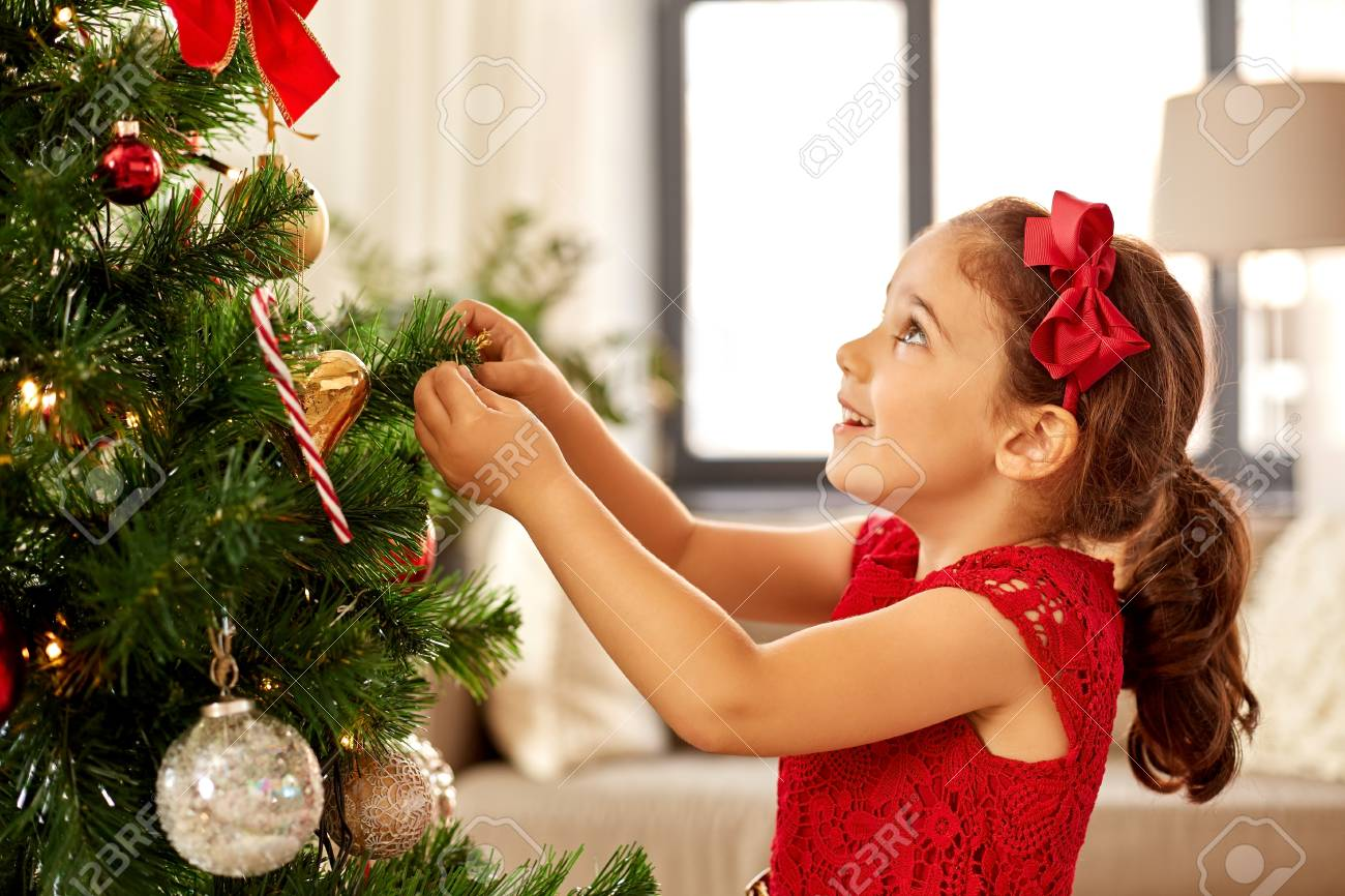 little girl decorating christmas tree at home - 108541753