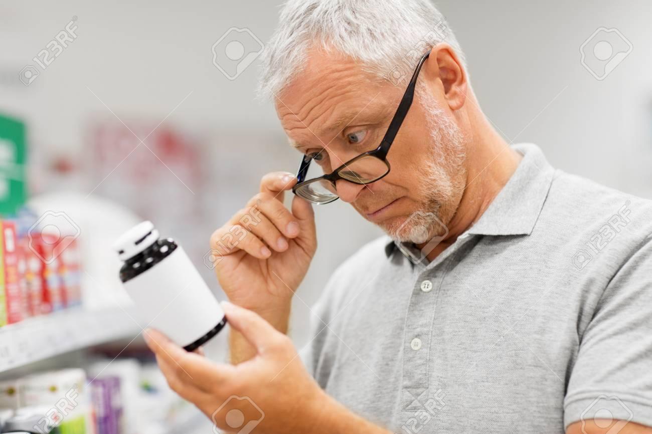 senior male customer with drug at pharmacy - 116790587