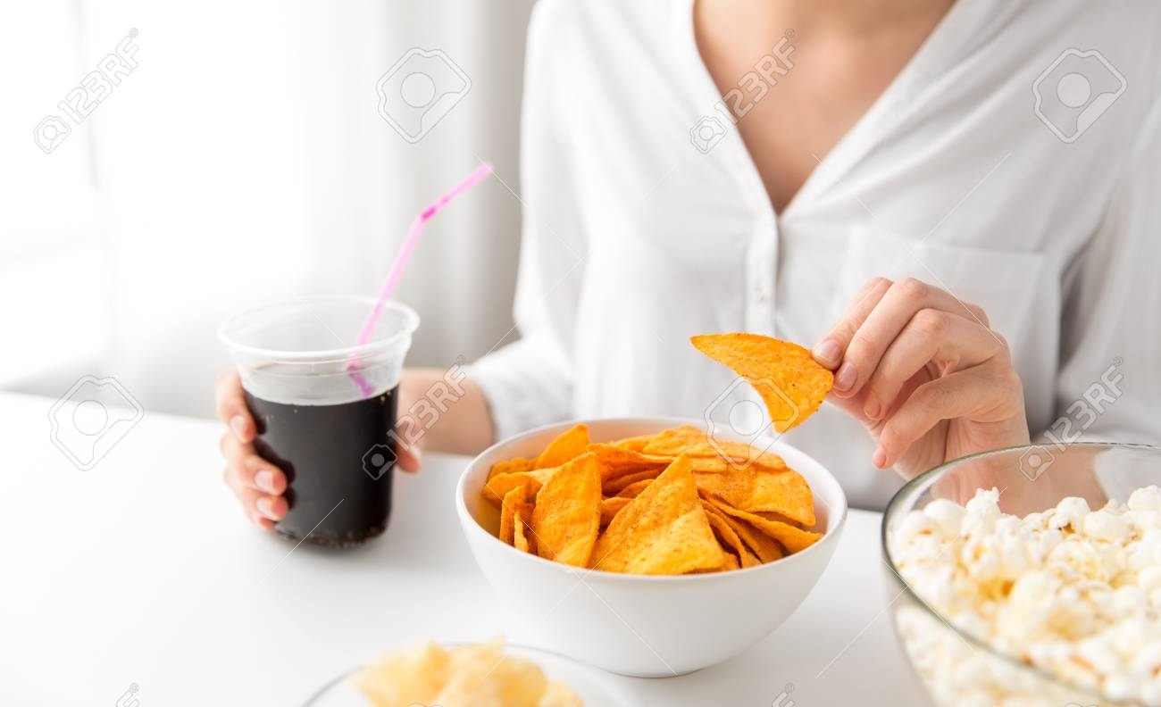 close up of woman eating corn nachos with cola - 120057876
