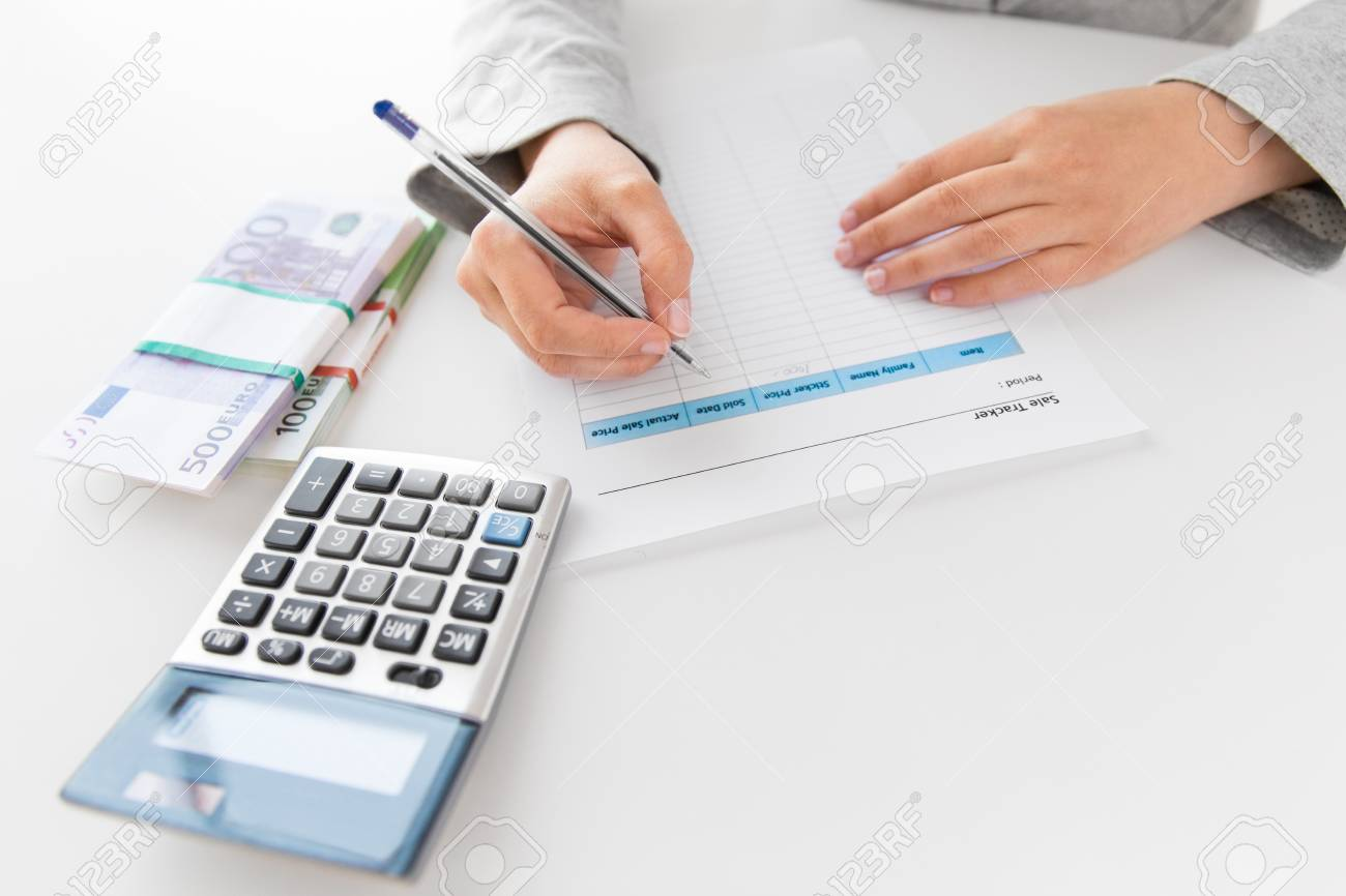 Hands with tax form, calculator and money on table
