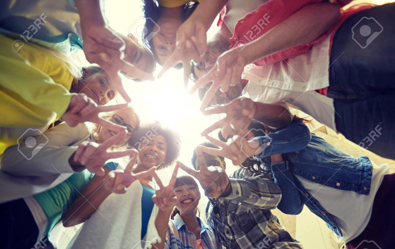 Education, friendship, gesture, victory and people concept - Group of happy international students or friends standing in circle and showing peace or v sign - 120888474