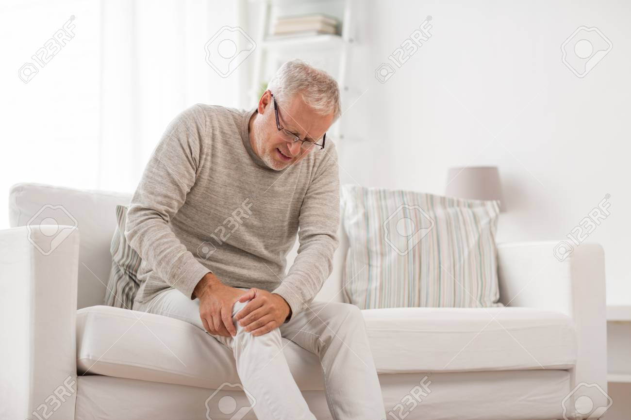 People, health care and problem concept - unhappy senior man suffering from knee ache at home - 120892758