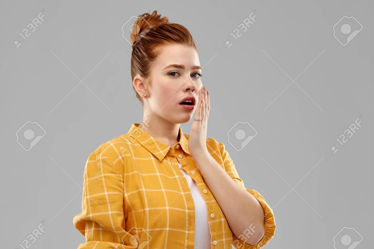 emotion, expression and people concept - red haired teenage girl in checkered shirt covering mouth by hands over grey background - 121162711