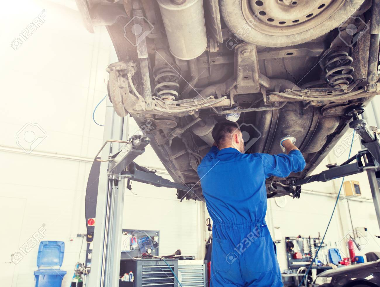 mechanic man or smith repairing car at workshop - 121881932