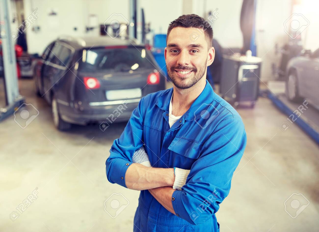 Happy auto mechanic man or smith at car workshop - 121996397