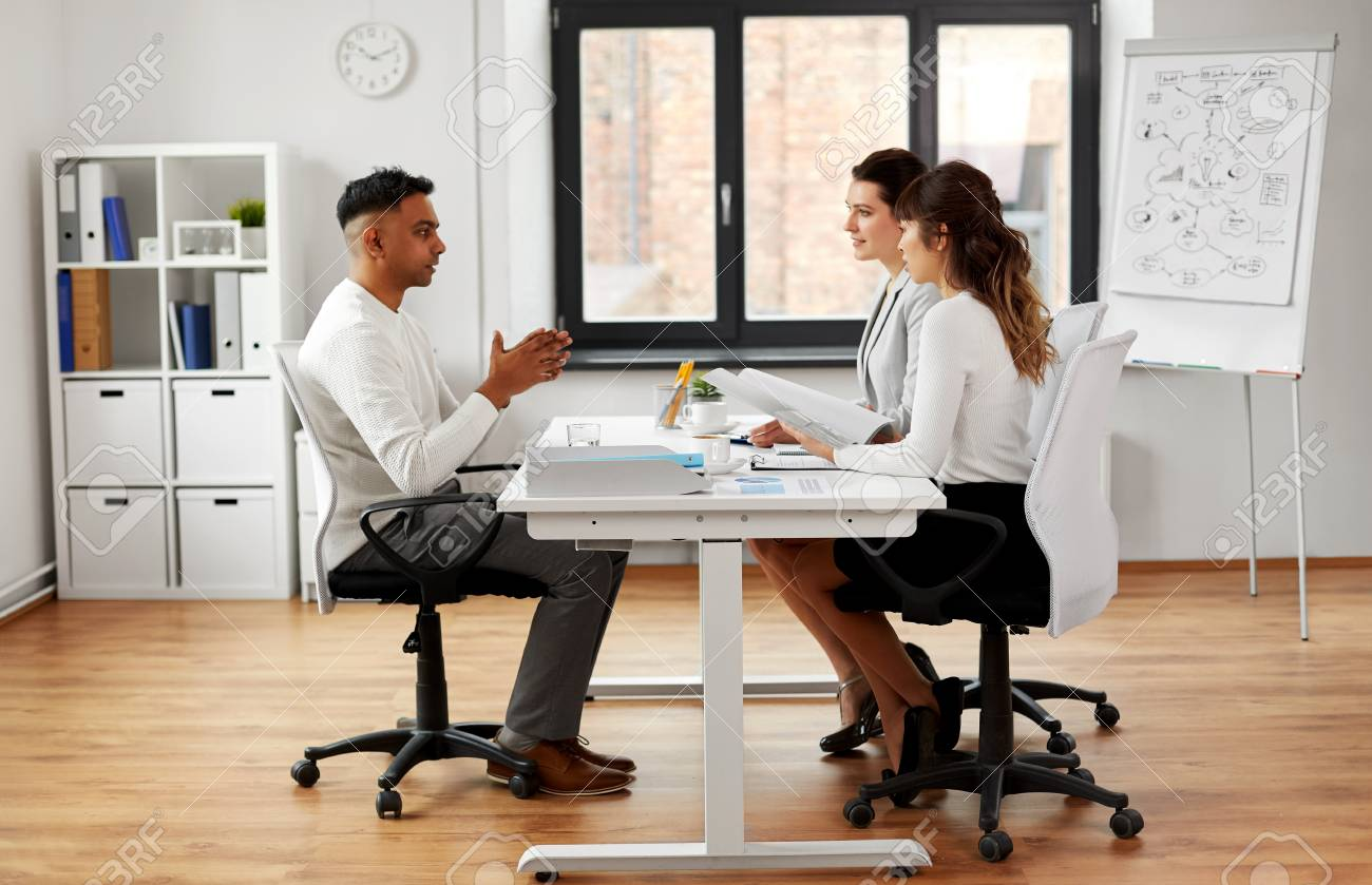 Recruiters having job interview with male employee - 121996703