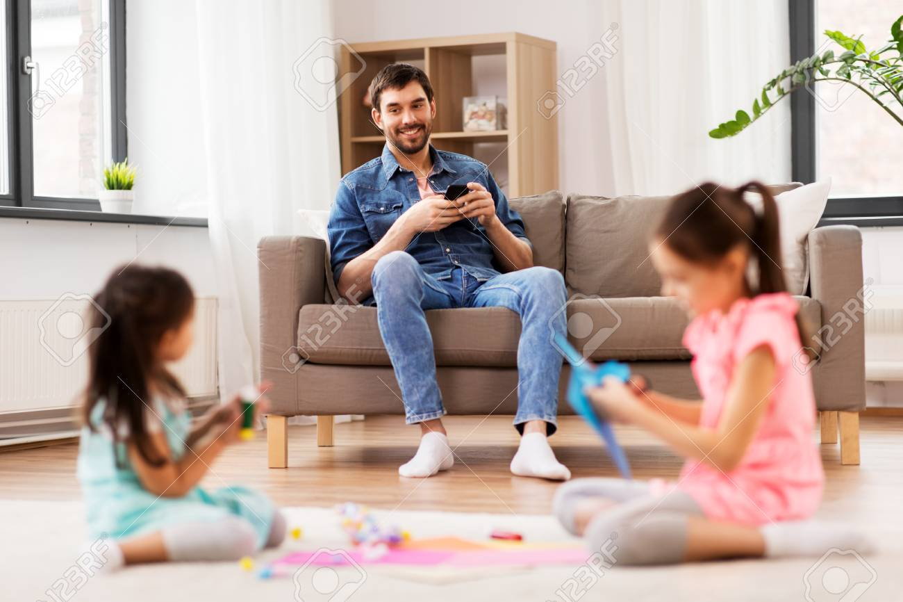 Father with smart phone looking at her daughters playing at home - 121996676