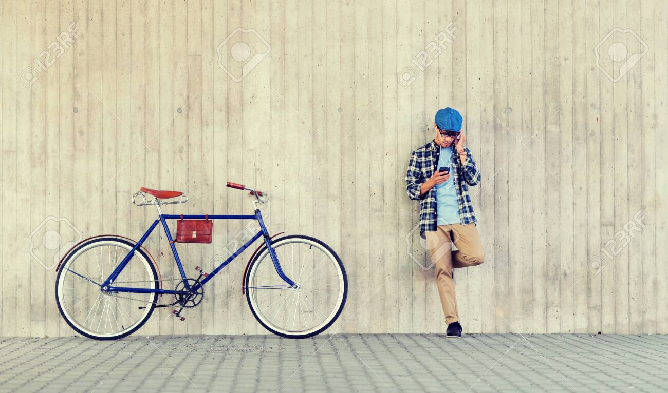 people, style, technology, leisure and lifestyle - young hipster man in earphones with smartphone and fixed gear bike listening to music at city street wall - 122209015