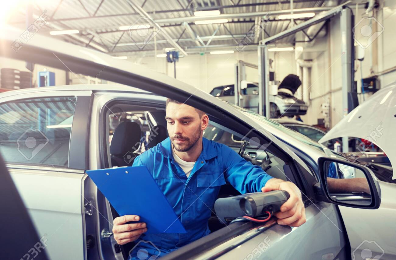 service, repair, maintenance and people concept - mechanic man with automotive diagnostic scanner and clipboard checking car system at workshop - 122209277