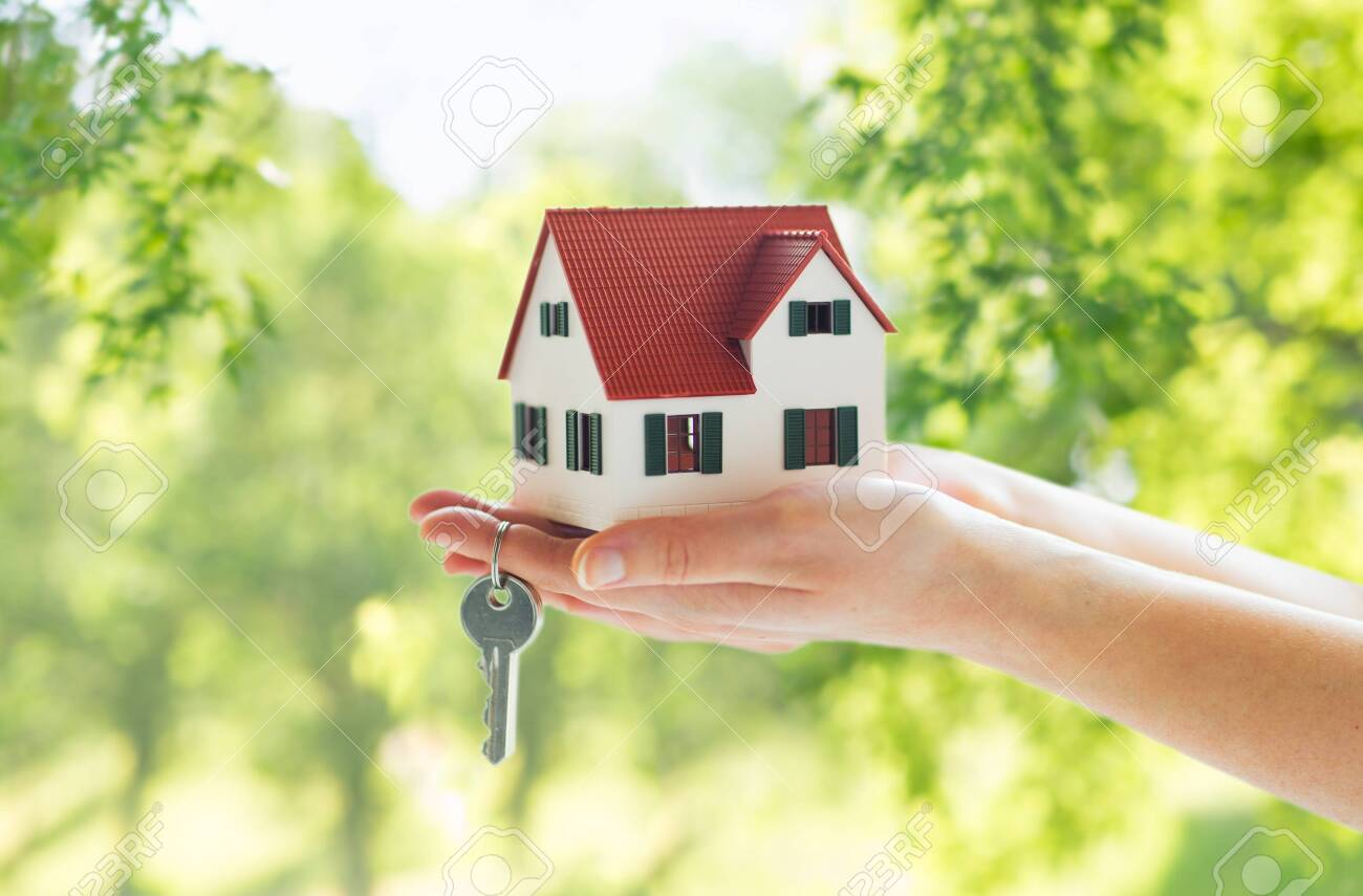 mortgage, real estate and property concept - close up of hands holding house model and home keys over green natural background - 122218481