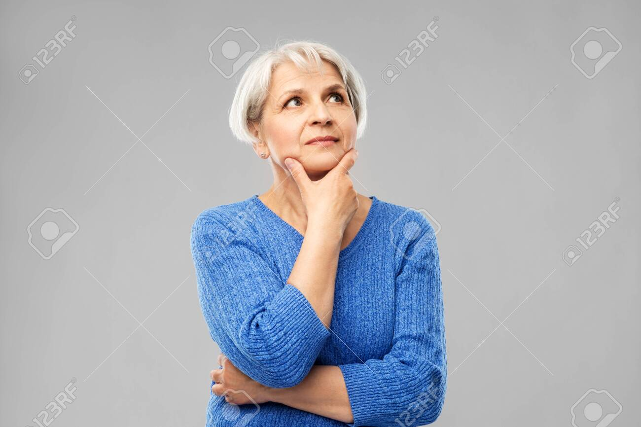 Old people and decision making concept - portrait of senior woman in blue sweater thinking over grey background - 122308265
