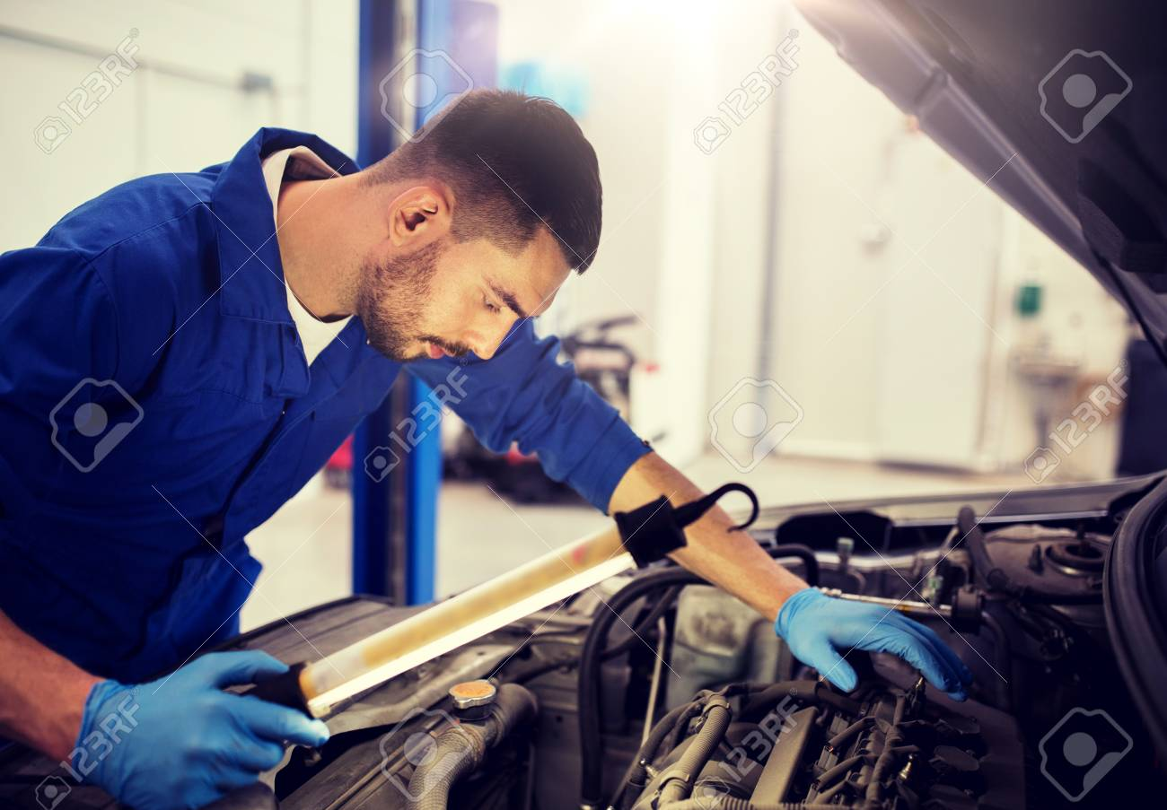 car service, repair, maintenance and people concept - auto mechanic man with lamp working at workshop - 122616461
