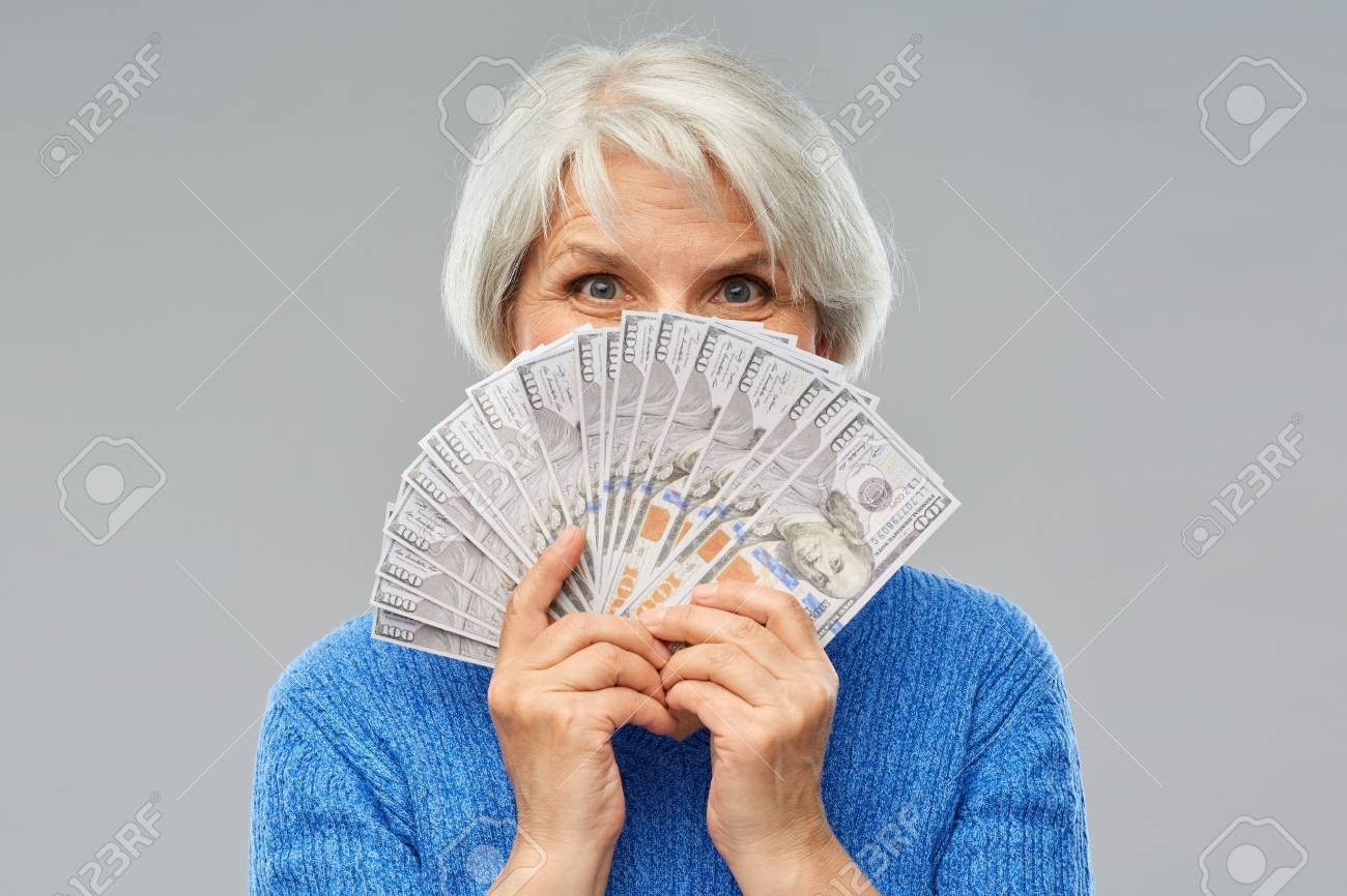 savings, finances and people concept - smiling senior woman hiding face behind hundreds of dollar money banknotes - 122616763