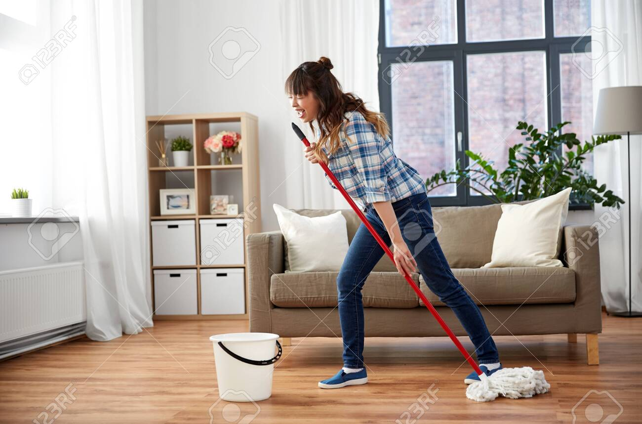 Happy Asian woman with mop cleaning floor at home - 122648883