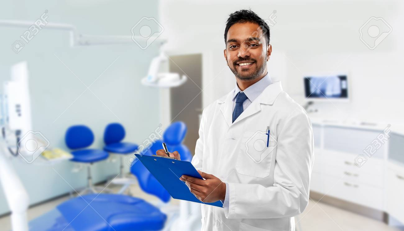 medicine, dentistry and healthcare concept - smiling indian male dentist in white coat with clipboard over dental clinic office background - 122978790