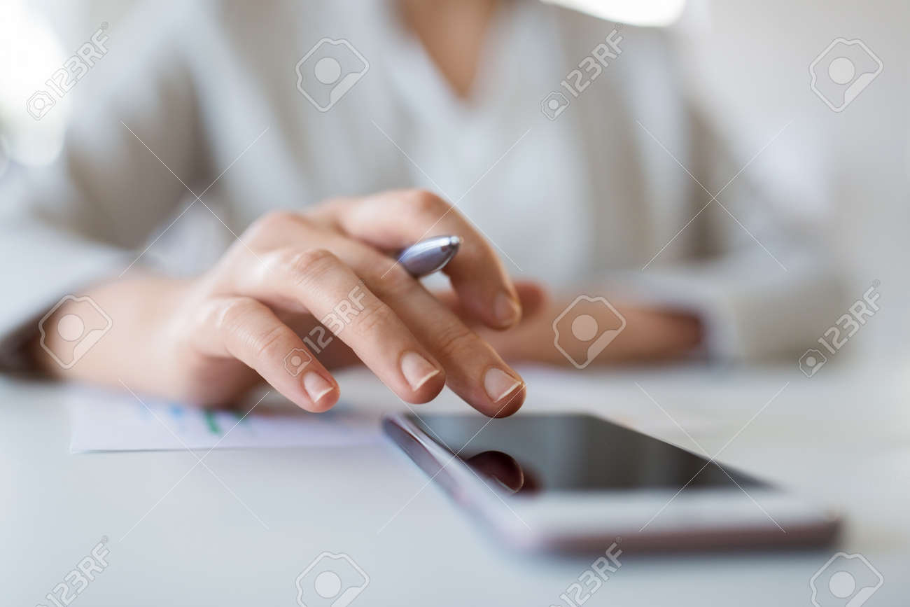 business, technology and people concept - close up of hand of businesswoman using smartphoner at office - 122979142