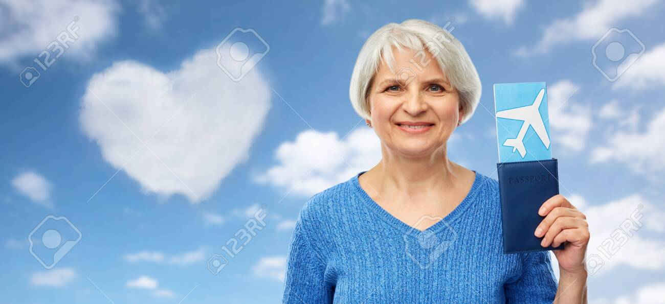 tourism, travel and vacation concept - happy senior woman with passport and airplane ticket over blue sky and clouds background - 123226064