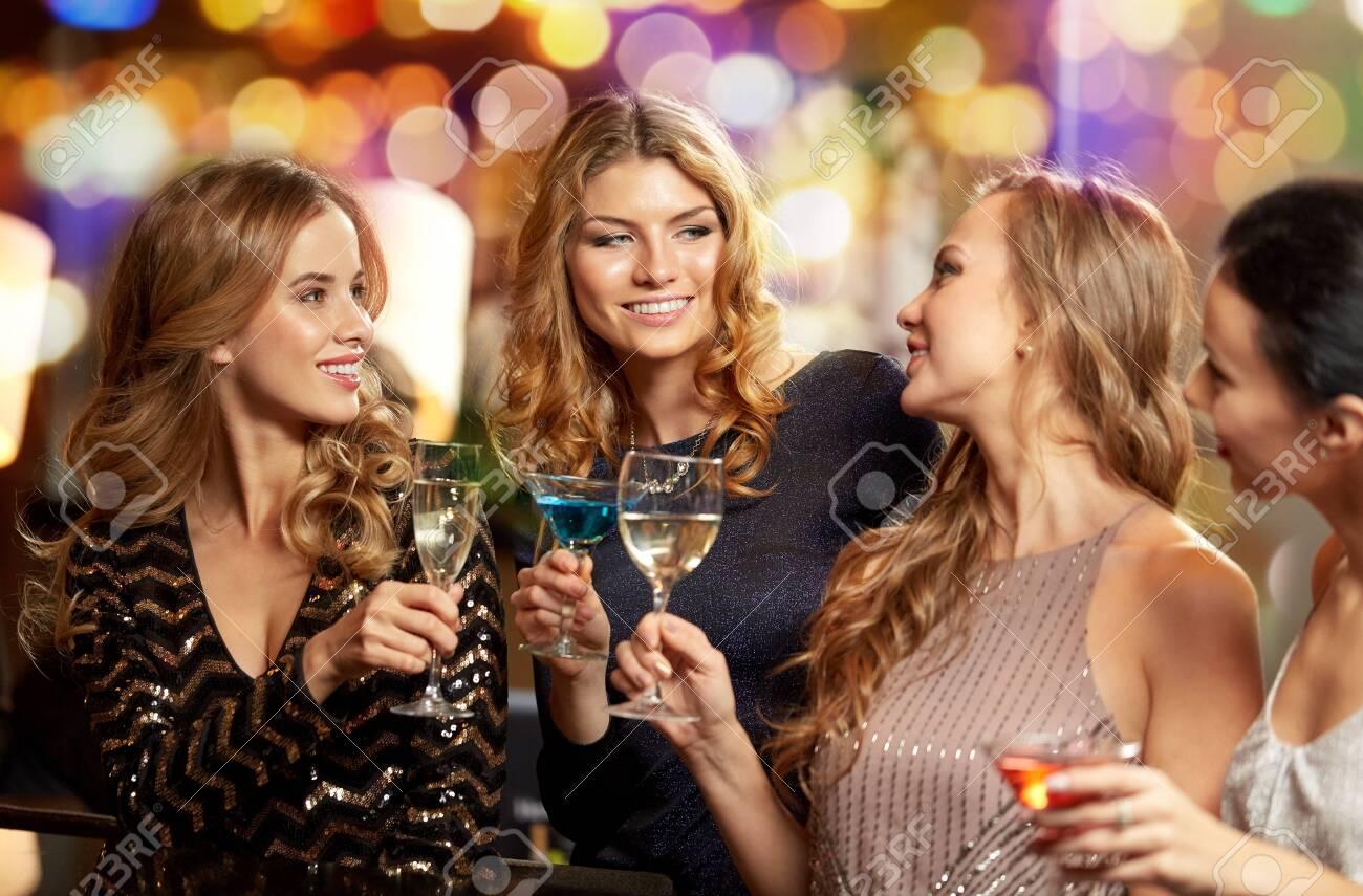 happy women clinking glasses at night club - 123559660