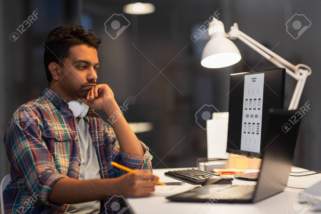 creative man with laptop working at night office - 123580626