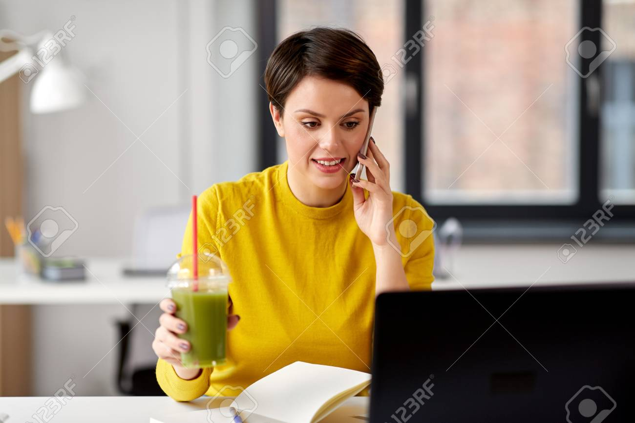 woman with drink calling on smartphone at office - 124767086