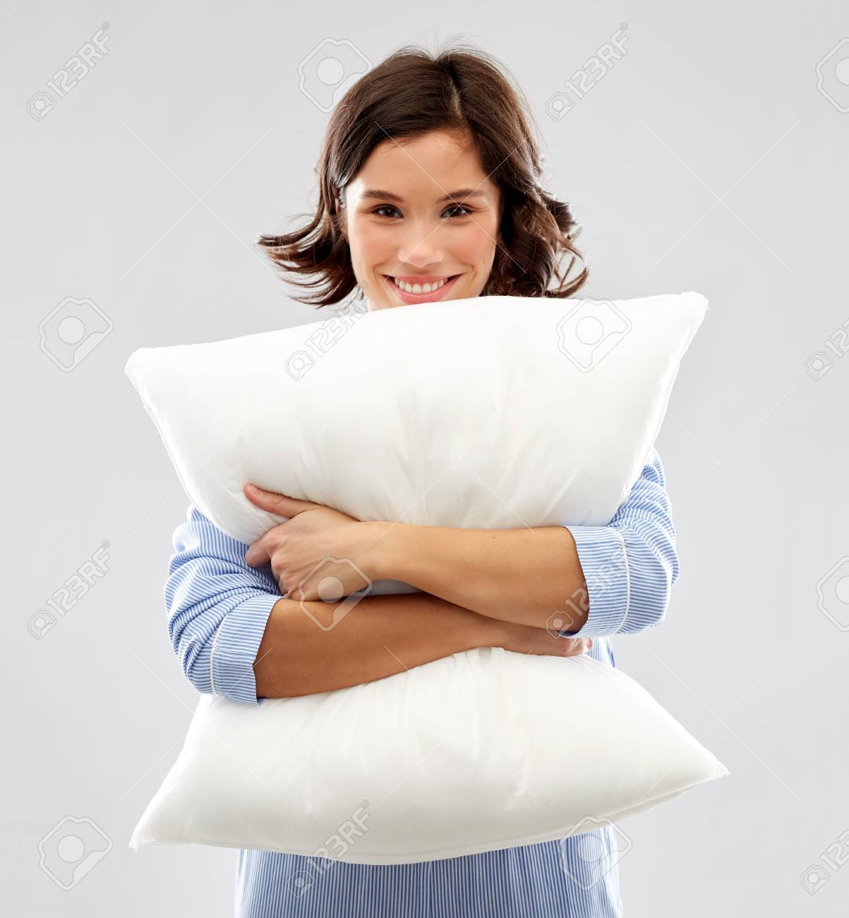 happy young woman in pajama hugging pillow - 124767093