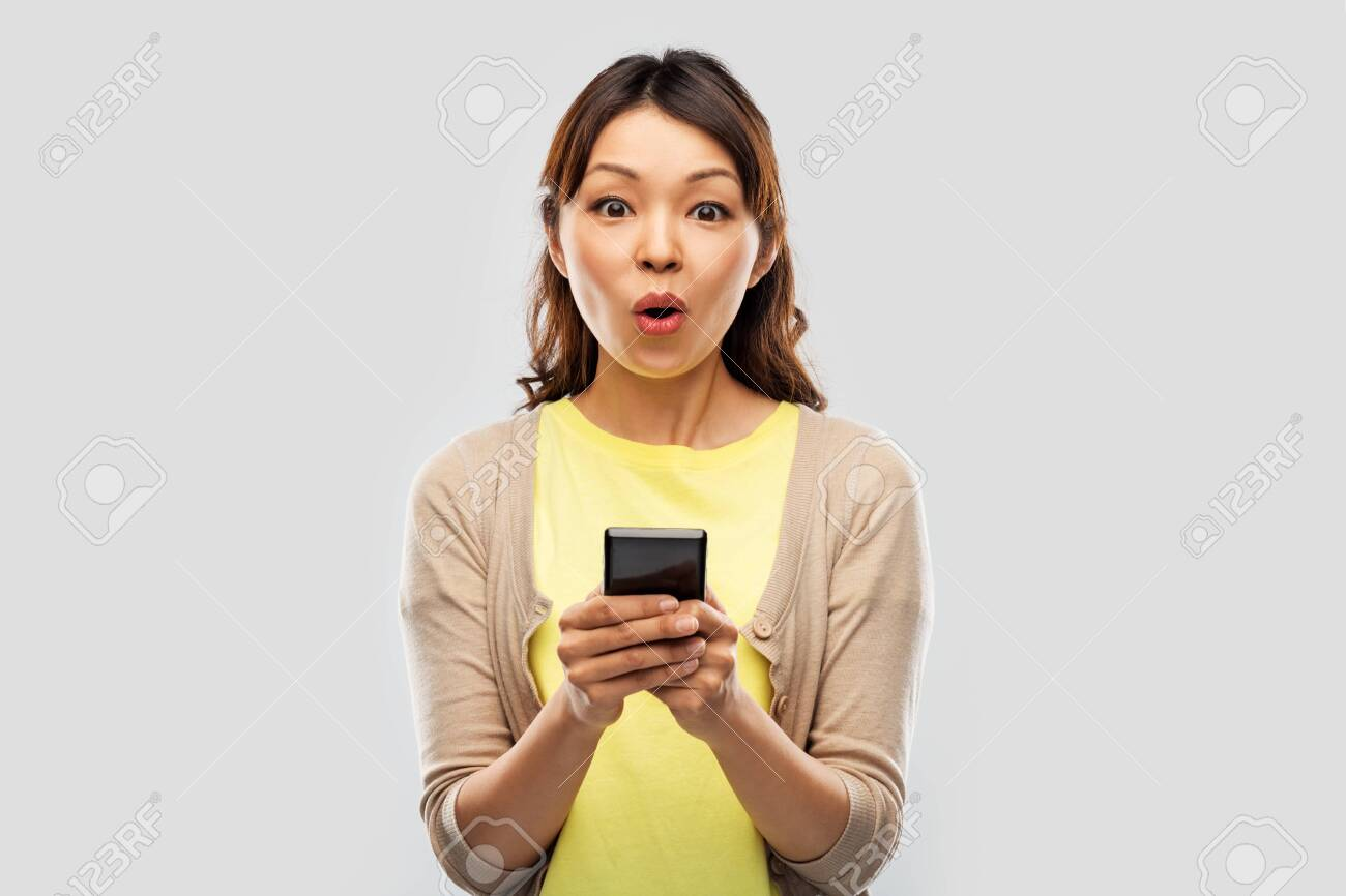 surprised asian woman using smartphone - 124311143