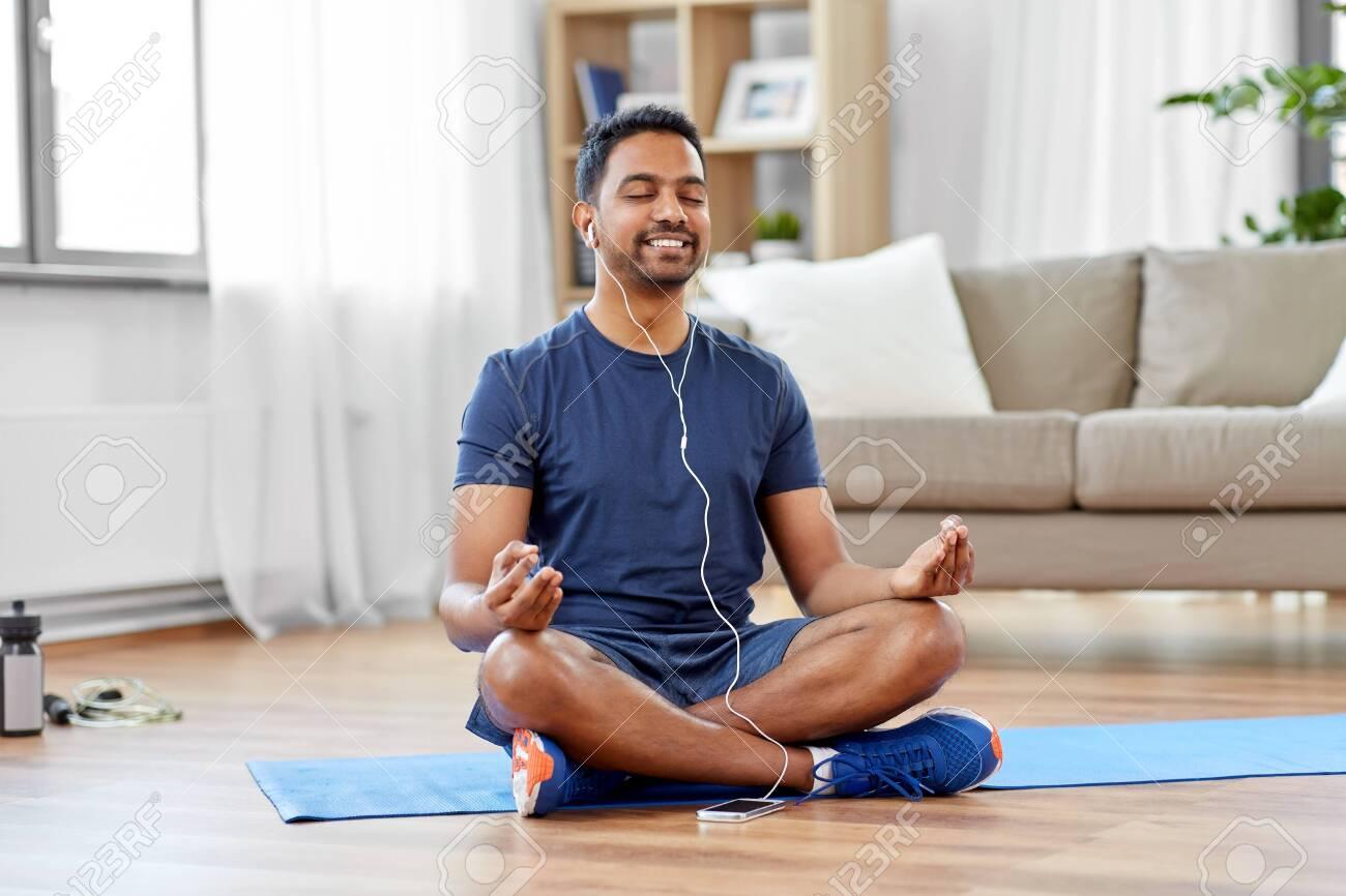 indian man meditating in lotus pose at home - 124311452