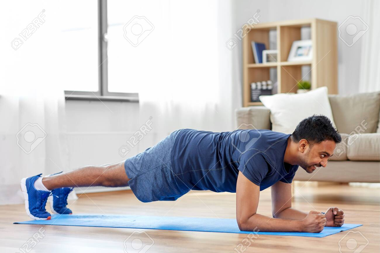 man doing plank exercise at home - 124311484