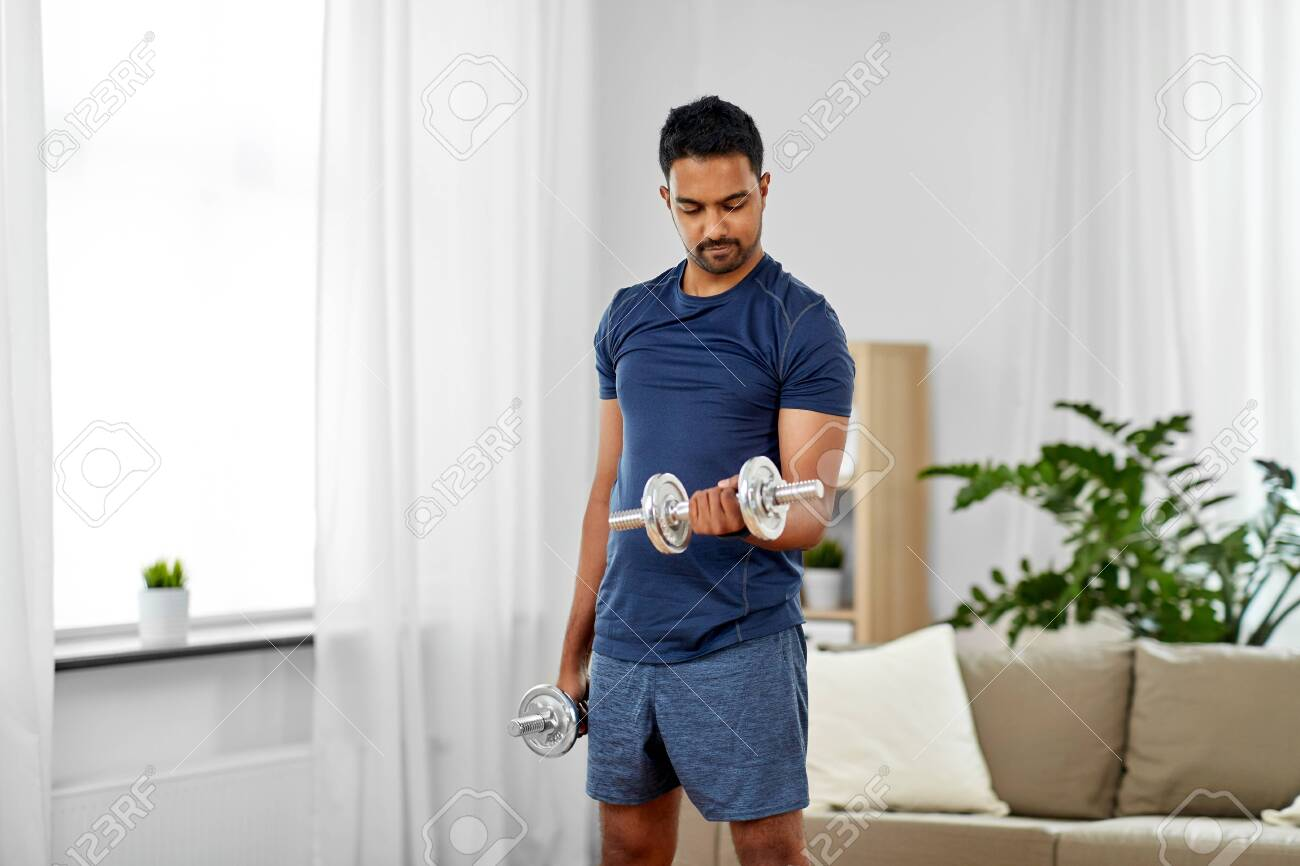 indian man exercising with dumbbells at home - 124629786