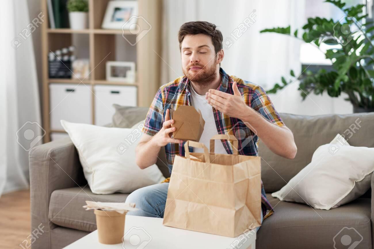 smiling man unpacking takeaway food at home - 124812960