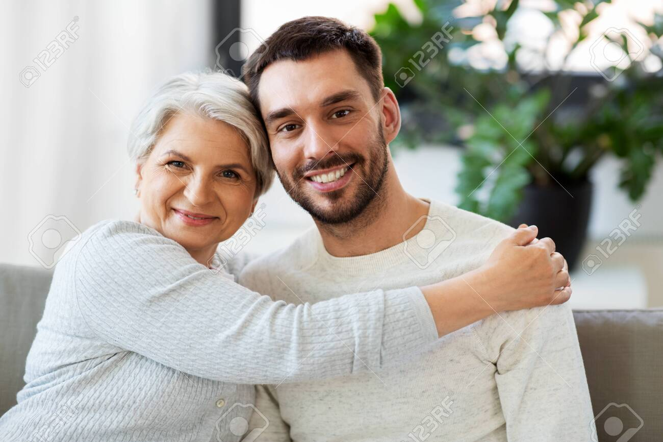 Senior mother with adult son hugging at home - 124940592