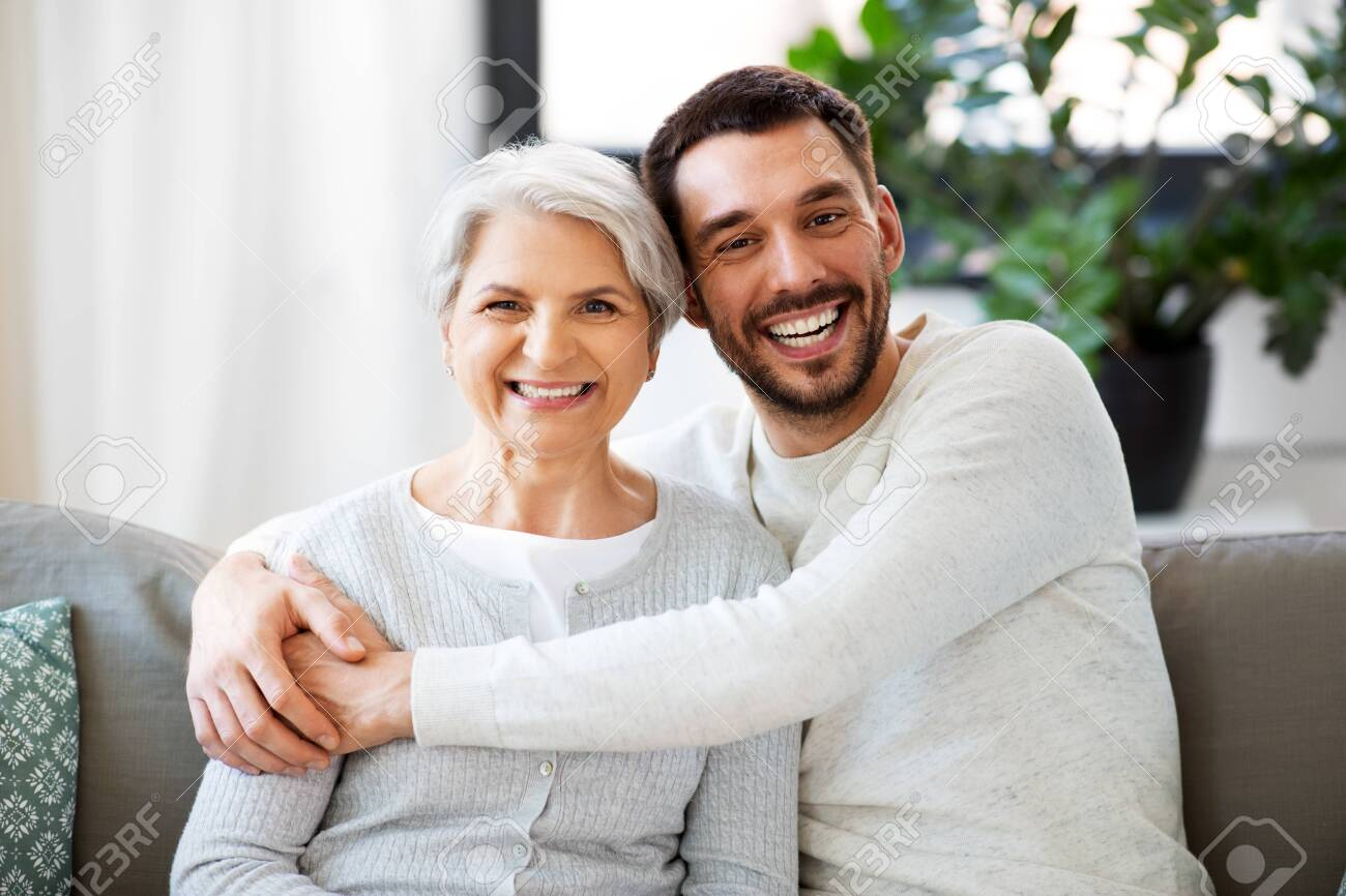 senior mother with adult son hugging at home - 125091533