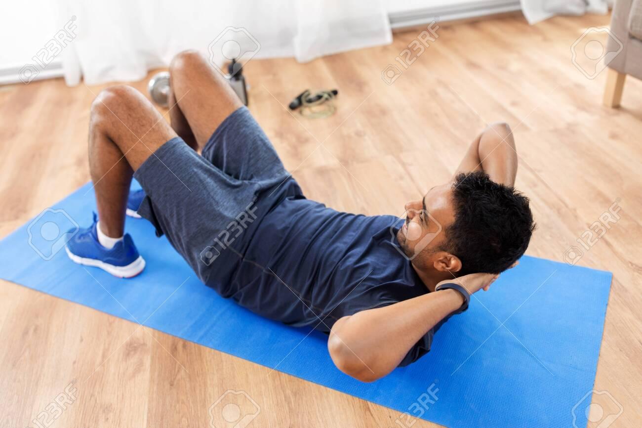 Indian man making abdominal exercises at home - 125188558