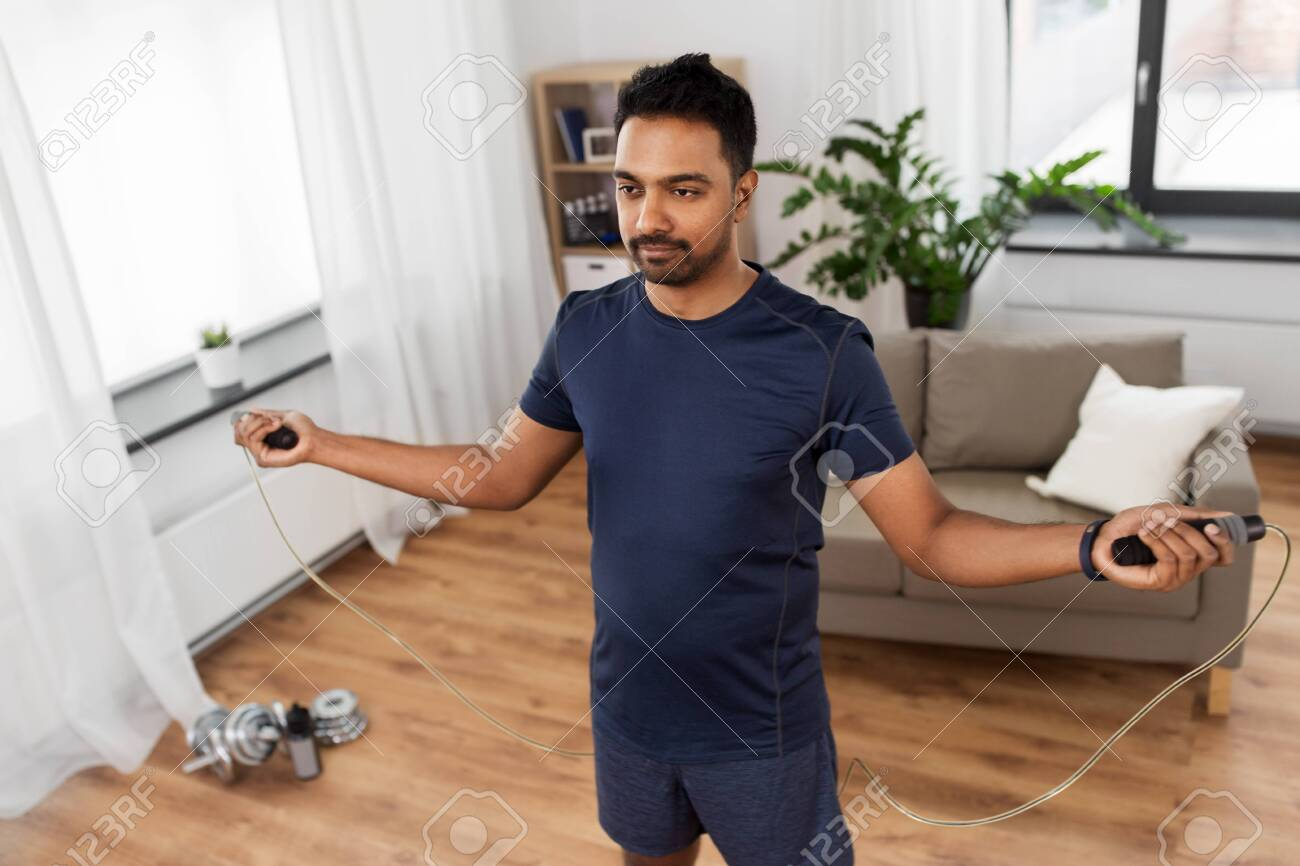 Indian man exercising with jump rope at home - 125188596