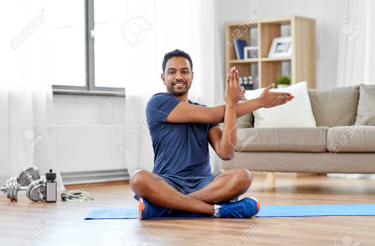 sport, fitness and healthy lifestyle concept - indian man training and stretching arm at home - 125557709